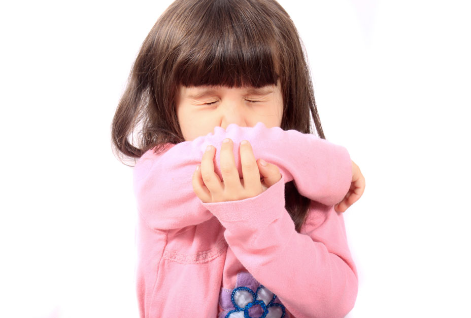 child coughing into elbow