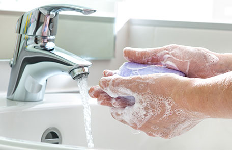 someone washing their hands with soap