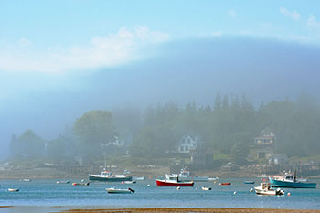 Mist rising over lobster boats in Maine harbor