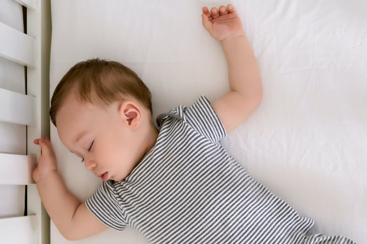 Photograph of baby sleeping on its back