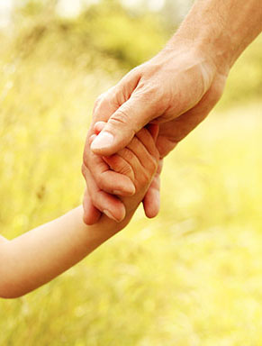 Closeup of adult holding child's hand