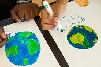 students drawing pictures of earth