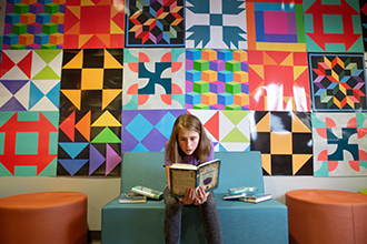 student sitting and reading a book