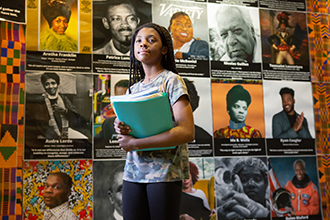 student standing with historical portraits behind