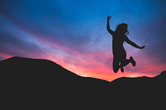 silhouette of girl jumping in the air with a sunset in the background