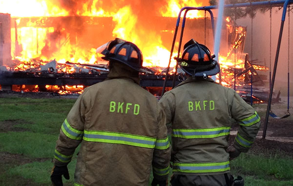 Photo of two firemen in front of fire
