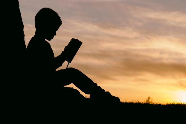 Photo of a boy reading at sunset