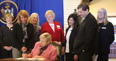 Photo of Governor Mills signing LD1