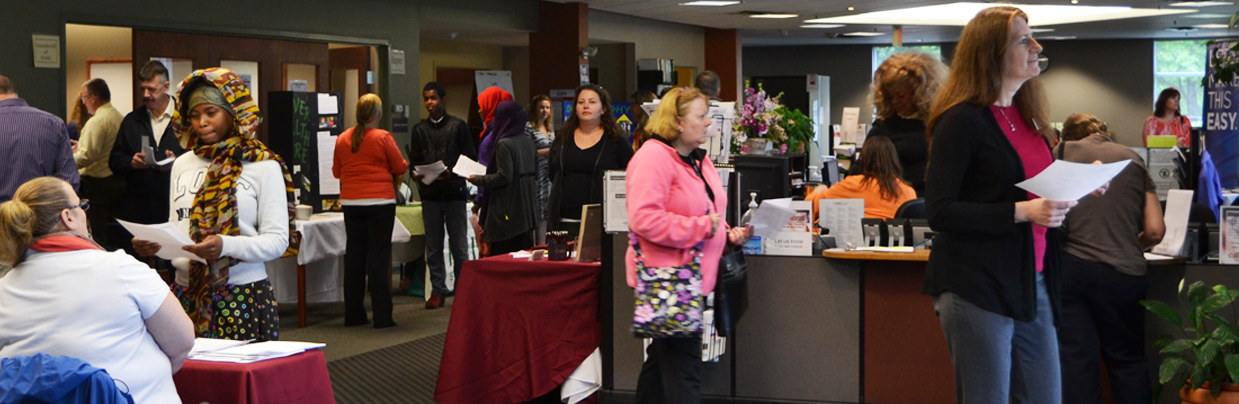 People walking around the CareerCenter, talking with employers at job fair exhibits