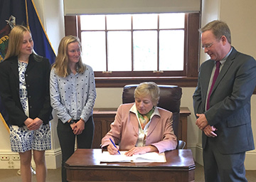 Rep. Brian Hubbell, D-Bar Harbor, and Ania Wright and Sara Lowgren (far left), youth climate leaders and students at College of the Atlantic, join Gov. Janet Mills as she signs LD 658. Sponsored by Hubbell, the measure puts Maine on a path to triple in-state renewable energy generation by 2030.