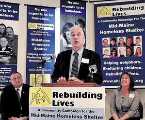 Mid-Maine Homeless Shelter Campaign Chairman Doug Cutchin speaks about fundraising progress for the new shelter in Waterville on Monday. Gov. Paul LePage and the Rev. Susan Reisert, campaign vice chairman, watch in the background.