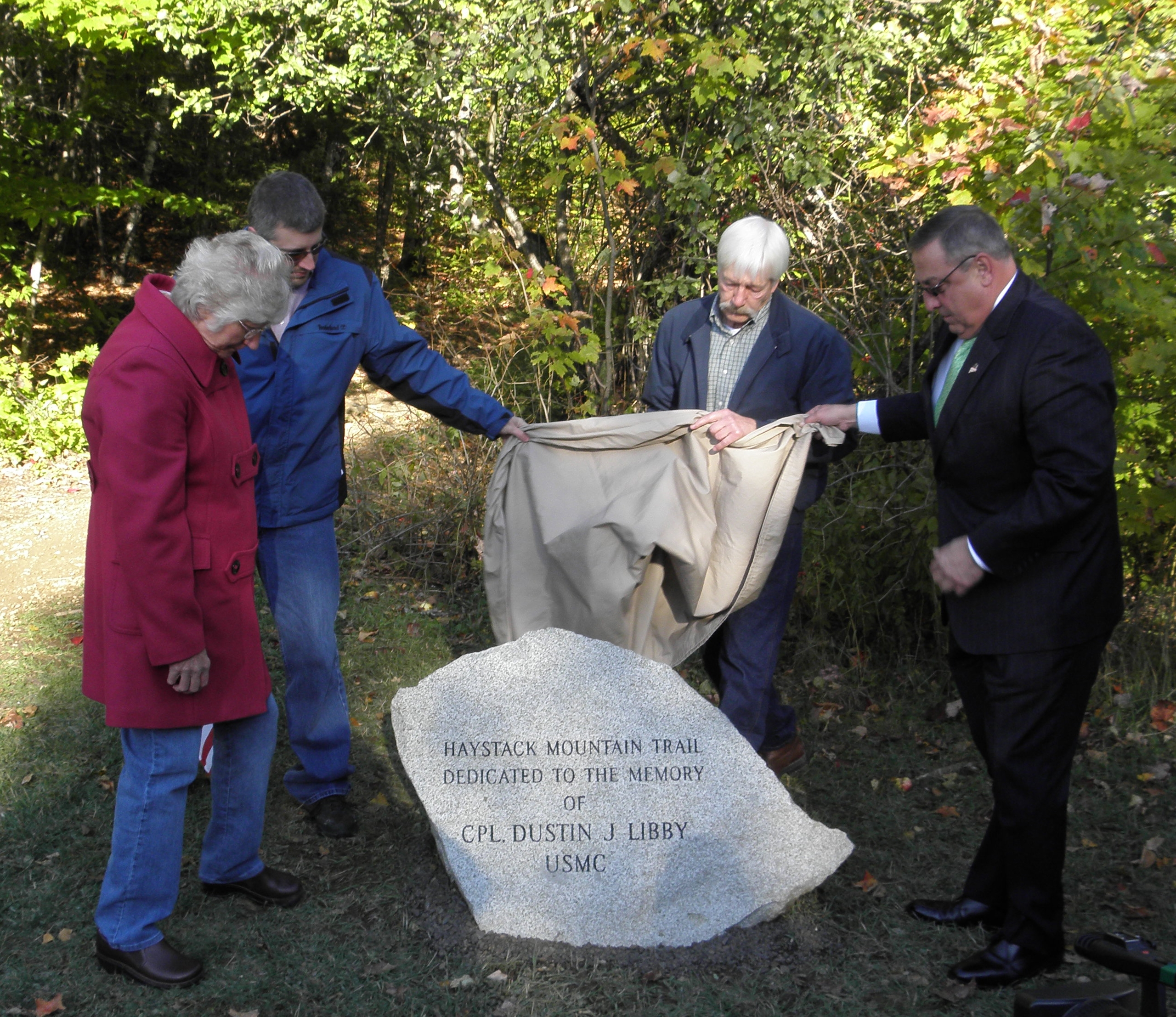 Governor Paul LePage (right) helps uncover a trailhead monument dedicated to Cpl. Dustin J. Libby, a Presque Isle native, who was killed in 2006 in Iraq while serving in the U.S. Marine Corps. Taking part in the unveiling ceremony were Libby's family (left to right), his mother, Geni Libby, brother Chris, and father, Judd Libby.