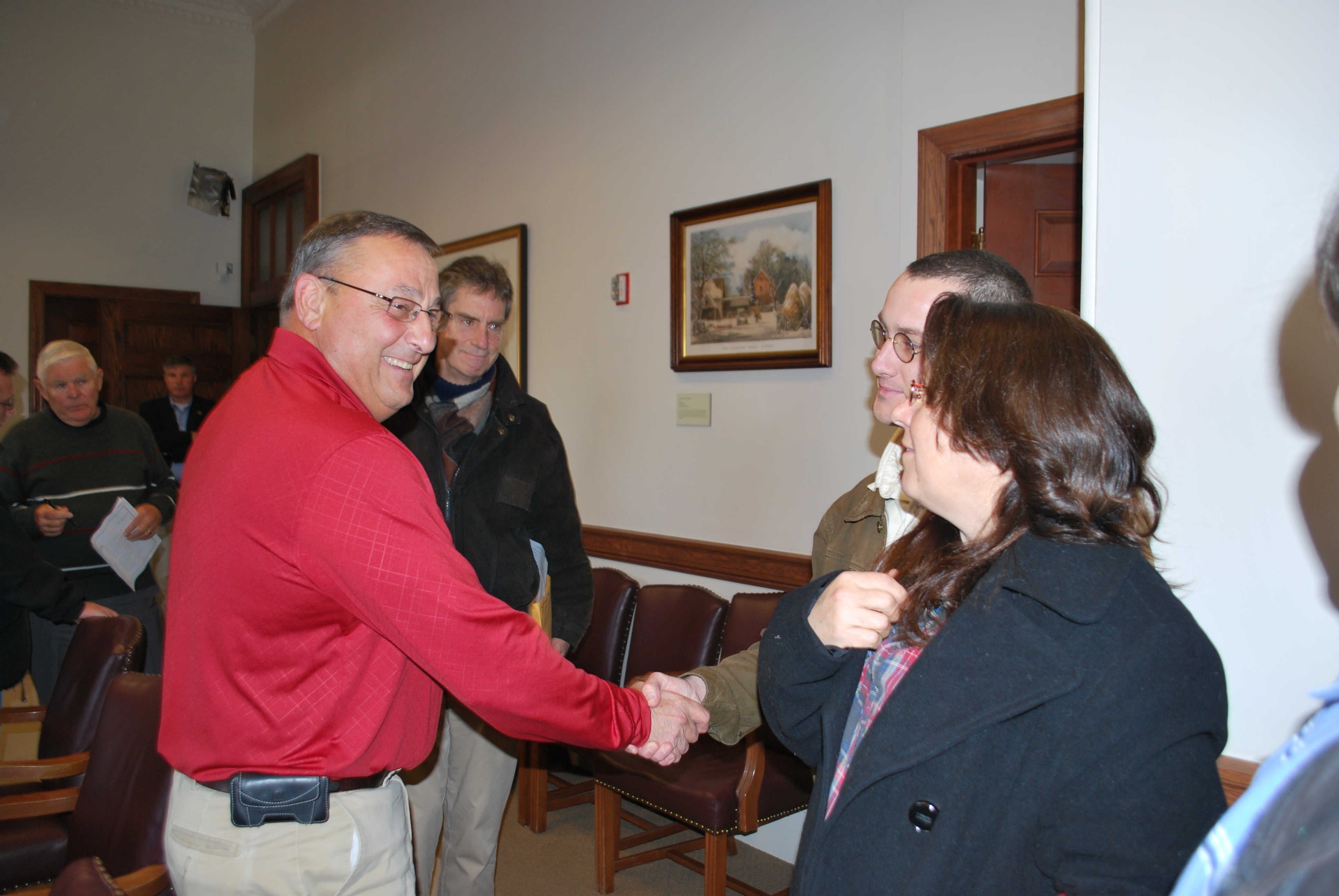 After the meeting, Governor LePage shakes hands with Rep. Andrew O'Brien and Brenda Akers. Wil Tibby can be seen to the right of the Governor and Commissioner Winglass is in the background